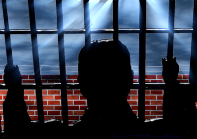 Mann hinter Gittern mit Blick nach außen auf eine Mauer