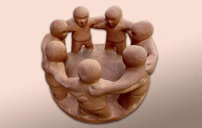 Gruppe steht im Kreis, umarmt einander