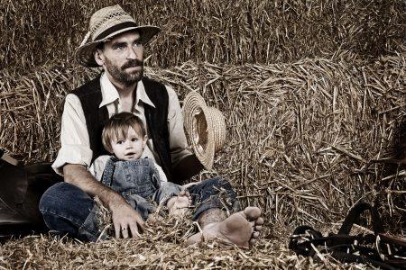 Vater mit kleinem Sohn au dem Schoß sitz vor Heuballen.